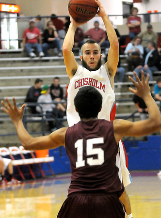 Chisholm's Branden Meier looks for an open Longhorn player as Blackwell's Oscar Sosa defends the lane Tuesday at the Paul J. Outhier Fieldhouse. (Staff Photo by BONNIE VCULEK)