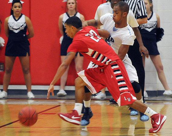 Enid's Aaron Austin pressures Lawton's #23 Saturday at the NOC-Enid Mabee Center. (Staff Photo by BILLY HEFTON)