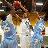 Enid's Jemarcus Jackson puts up a shot against Lawton Ike's James Cross and Deonte Menetee Friday at the NOC-Enid Mabee Center. (Staff Photo by BILLY HEFTON)