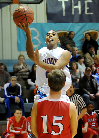 Justus Crites of Waukomis avoids Dover's Zach Bell to score a fast break basket Tuesday at Waukomis High School. (Staff Photo by BILLY HEFTON)