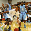 Enid's Keon Parker looks for an opening against Lawton Ike's Keyshaun Perkins Friday at the NOC-Enid Mabee Center. (Staff Photo by BILLY HEFTON)