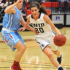 Enid's Andi Pierce drives the lane against Lawton Ike's McKenzie Madigan Friday at the NOC-Enid Mabee Center. (Staff Photo by BILLY HEFTON)