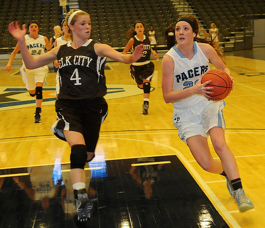 Enid Pacers' Andi Pierce sprints toward the bucket as Elk City's Mikayla Harrison tries to cut Pierce off before she can score during the Pacers' 45-39 overtime win in the inaugural basketball game at the Enid Event Center Friday, Dec. 6, 2013. (Staff Photo by BONNIE VCULEK)