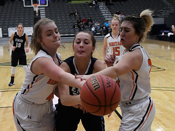 Enid's Izzy Plunkett battles Heritage's Faith Rohrbough and Hannah Watkins for the ball Thursday December 29, 2016 during the first round of the 1st Enid Holiday Classic at the Central National Bank Center. (Billy Hefton / Enid News & Eagle)