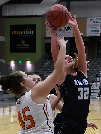 Enid's Sarah Johnson shoots over Heritage's Shelby Cook Thursday December 29, 2016 during the first round of the 1st Enid Holiday Classic at the Central National Bank Center. (Billy Hefton / Enid News & Eagle)