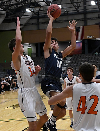 Enid's Orion Tafoya goes to the basket against Heritage's Seth Stanley and Ryan Heiligenthal Thursday December 29, 2016 during the first round of the 1st Enid Holiday Classic at the Central National Bank Center. (Billy Hefton / Enid News & Eagle)