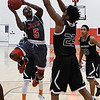NOC Enid's Dyaire Holt drives to the basket against Sunrise Academy's Derrick Walker Thursday December 8, 2016 at the NOC Mabee Center. (Billy Hefton / Enid News & Eagle)