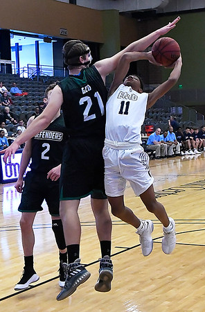 Enid's Darrin Ryan challenges Green Country's Marshall Elias Prescott in the lane during the Enid Holiday Classic Basketball Tournament Friday December 29, 2017 at the Central National Bank Center. (Billy Hefton / Enid News & Eagle)