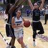 Enid's Elizabeth Plunkett drives to the basket against Choctaw's Makayla White and Mackenzie Crusoe Tuesday December 19, 2017 at the Central National Bank Center. (Billy Hefton / Enid News & Eagle)