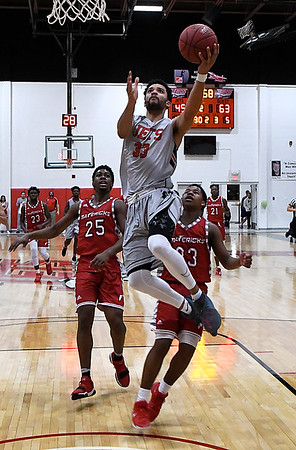 NOC Enid's Tony Hall gets behind NOC Tonkawa defenders Trevion Lamar and Chris Hamil for a basket Wednesday December 6, 2017 at the NOC Mabee Center. (Billy Hefton / Enid News & Eagle)