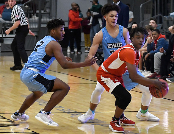 Enid's Telin Phillips and Carter Owens pressure Hoops For Christ's Brandyn Dempsey during the first round of the Enid Holiday Classic Thursday December 27, 2018 at the Central National Bank Center. (Billy Hefton / Enid News & Eagle)