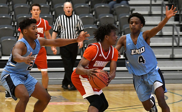 Enid's Telin Phillips and Carlos Menefield pressure Hoops For Christ's Brandyn Dempsey during the first round of the Enid Holiday Classic Thursday December 27, 2018 at the Central National Bank Center. (Billy Hefton / Enid News & Eagle)