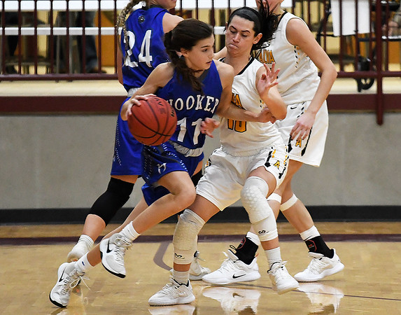 Hooker's Hollie Stalder is pressured by Alva's Hallie Durkee during the championship game of the Mustang Stampede at Pioneer High School Friday December 7, 2018. (Billy Hefton / Enid News & Eagle)