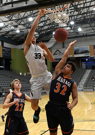 Enid's Cyson Mathis dunks the ball over Heritage's Keith Saucier during a semi-final of the Enid Holiday Classic Friday December 28, 2018 at the Central National Bank Center. (Billy Hefton / Enid News & Eagle)