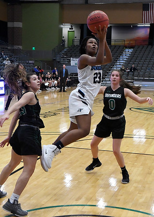 Enid's Mya Edwards puts up a shot in the lane between Green Country defenders Emily Prather and Abbey Phibbs during the consolation finals of the Enid Holiday Classic Saturday December 29, 2018 at the Central National Bank Center. (Billy Hefton / Enid News & Eagle)