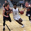Enid's Telin Phillips drives to the basket against Heritage's Ethan Carpenter and Caedon Snider during a semi-final of the Enid Holiday Classic Friday December 28, 2018 at the Central National Bank Center. (Billy Hefton / Enid News & Eagle)
