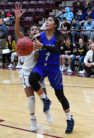 Hooker's Aliyah Pinon gets pass Alva's Rianna Clark for a shot during the championship game of the Mustang Stampede at Pioneer High School Friday December 7, 2018. (Billy Hefton / Enid News & Eagle)