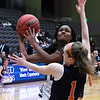 Enid's Mya Edwards drives the lane against Heritage's Pam Seiler during the first round of the Enid Holiday Classic Thursday December 27, 2018 at the Central National Bank Center. (Billy Hefton / Enid News & Eagle)