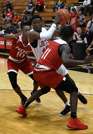 NOC Enid's Rance Kendrick tries to drive between NOC Tonkawa's J.D. Ray and Tyrel Morgan Thursday, December 5, 2019 at the NOC Mabee Center. (Billy Hefton / Enid News & Eagle)
