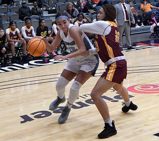Enid's Lanie Goins drives towards the basket against Putnam City North's Amaya Chandler Tuesday, December 3, 2019 at the Stride Bank Center. (Billy Hefton / Enid News & Eagle)