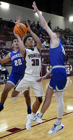 Pioneer's Kevin Noel drives to the basket between Hooker's Carson Maloney and Johnny Ugarte during the finals of the Mustang Stampede Tournament Saturday, December 7, 2019 at Pioneer High School. (Billy Hefton / Enid News & Eagle)