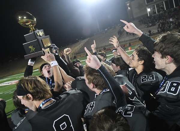 Members of the Pond Creek-Hunter football team lift the championship trophy after defeating Waynoka 54-8 to win the Class C state championship Friday, December 6, 2019 at Northwestern Oklahoma State University in Alva. (Billy Hefton / Enid News & Eagle)