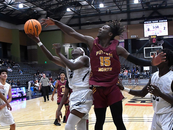 Enid's Sam Hill is defended by Putnam City North's Kayhon Russell Tuesday, December 3, 2019 at the Stride Bank Center. (Billy Hefton / Enid News & Eagle)