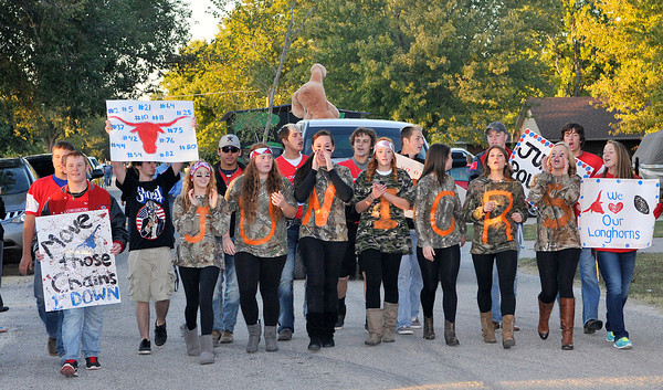 Members of the Chisholm High School junior class march through the streets of North Enid Thursday during the homecoming parade. (Staff Photo by BILLY HEFTON)