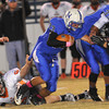 Tonlawa's Benjamin Hook tries to hang onto Hennessey's Tabor Johns during the first quarter Friday at Hennessey High School. (Staff Photo by BILLY HEFTON)