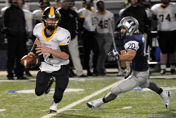 Sand Springs quarterback, Cody Hale, avoids the rush of Enid's Sam Clemens Friday at D. Bruce Selby Stadium. (Staff Photo by BILLY HEFTON)