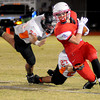 Chisholm's Danner Kiernan (3) drags Tonkawa's Bryan Jordan (73) and Chase Pfluger (27) as he sprints around the end during the Longhorns' 33-8 win over the Buccaneers Friday, Nov. 8, 2013. (Staff Photo by BONNIE VCUELK)
