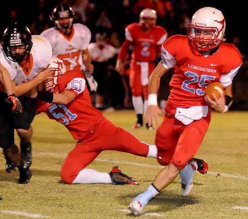 Chisholm's Britton Yunker picks up a first down during the Longhorns' win over the Tonkawa Buccaneers at Chisholm High School Friday, Nov. 8, 2013. (Staff Photo by BONNIE VCULEK)