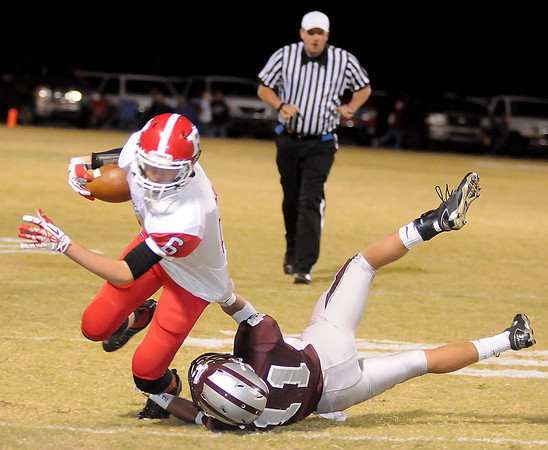 Garber's Dallas Hunt tackles Ringwood's Cole Swart during the Wolverines' 28-18 win over the Red Devils at Garber Friday, Nov. 1, 2013. (Staff Photo by BONNIE VCULEK)