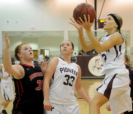 Pioneer's Shelby Flavell (right) sails to the bucket for two as teammate, Andi Simunek (center) and Morrison's Rissa Inselman (left) battle for position under the bucket during the OSSAA District elimination games at Pioneer High School Friday, Feb. 15, 2013. The Morrison Lady Wildcats defeated the Pioneer Lady Mustangs 46-42. (Staff Photo by BONNIE VCULEK)