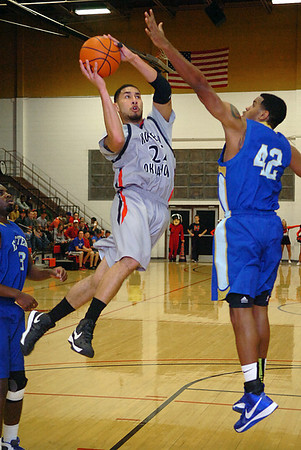 NOC's Jeremy Espinoza leaps toward the basket against Eastern's Iman Johnson Monday at the NOC Mabee Center. (Staff Photo by BILLY HEFTON)