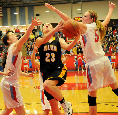 Alva's Jaden Hobbs drives inside for two against Chisholm's Morgan Lawver (left) and Nicole Middleton (right) at the Paul J. Outhier field house Friday, Feb. 1, 2013. (Staff Photo by BONNIE VCULEK)