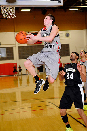 NOC's Connor Brooks goes under the basket to score against Western's D'Audrio Monday at the NOC Mabee Center. (Staff Photo by BILLY HEFTON)