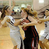 Morrison's Rissa Inselman grabs a rebound as Pioneer's Carli Woolsey, Lexsie Mann and Shelby Flavell defend during the OSSAA District Basketball playoffs at Pioneer High School Friday, Feb. 15, 2013. (Staff Photo by BONNIE VCULEK)