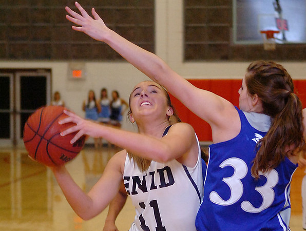 Enid's Abby Lee puts up a shot while defended by Guthrie's Cassidy Jones Tuesday at the NOC Mabee Center. (Staff Photo by BILLY HEFTON)