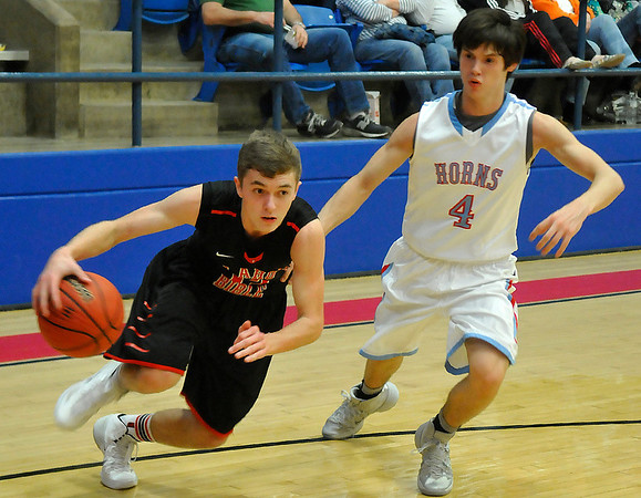 OBA's Camden Roggow drives pass Chisholm's Trevor Galusha Tuesday at Chisholm High School. (Staff Photo by BILLY HEFTON)
