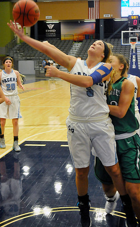 Enid's Haven Bay is pushed from behind as she shoots against Bishop McGuinness Tuesday at the Enid Event Center. (Staff Photo by BILLY HEFTON)