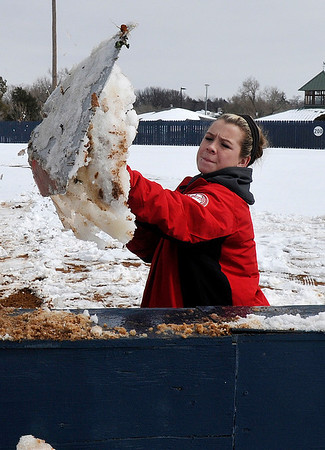 NOC Enid softball player, Shyanna Sigman, throws a shovelful of snow over a wall at Meadowlake Park Wednesday. The team was trying to clear the field for the season opener scheduled for Friday. (Staff Photo by BILLY HEFTON)