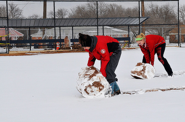 NOC Enid softball players,            , roll a snow balls across the infield at Meadowlake Park Wednesday. The team was trying to clear the field for the season opener scheduled for Friday. (Staff Photo by BILLY HEFTON)