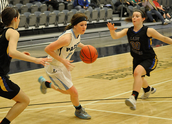 Enid's Andi Pierce drives toward the basket between two Stillwater defenders Tuesday at the Enid Event Center. (Staff Photo by BILLY HEFTON)