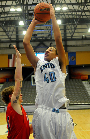 Enid's Devon Edwards puts up a shot over Lawton' Chris Jones Monday at the Enid Event Center. (Staff Photo by BILLY HEFTON)