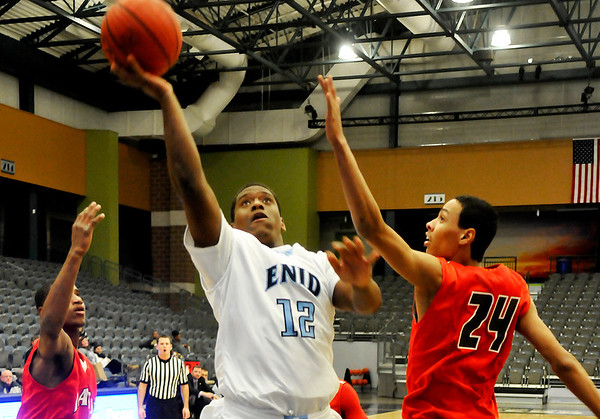 Enid's Raeshaan Finley puts up a shot against Lawton' Chris Deck Monday at the Enid Event Center. (Staff Photo by BILLY HEFTON)