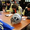 Enid High School Plainsmen football players (from left) Stephen Hocker, Sam Clemens and Mason Camp, sign their football letters of intent in the library at Enid High Wednesday, Feb. 5, 2014. (Staff Photo by BONNIE VCULEK)