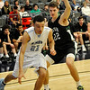 Enid's Randy Porter drives pass Josh Waters of Bishop McGuinness Tuesday at the Enid Event Center. (Staff Photo by BILLY HEFTON)