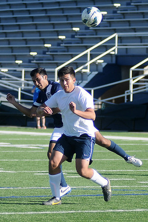 Enid's Felix Mora (back left) takes a shot on goal and scores against Plainsmen alum Angel Chavez during the annual alumni game at D. Bruce Selby Stadium Saturday, Feb. 22, 2014. (Staff Photo by BONNIE VCULEK)