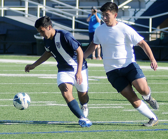 Felix Mora makes a shot on goal against Angel Chavez during the Plainsmen's Alumni game at D. Bruce Selby Stadium Saturday, Feb. 22, 2014. (Staff Photo by BONNIE VCULEK)